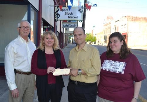 Richard Hawley (left), president of the Huntington County Council on Aging, and Holly Saunders (second from left), the council's executive director, accept gift certificates from Justin and Cynthia Wall, owners of the Opera Block Market, as door prizes.