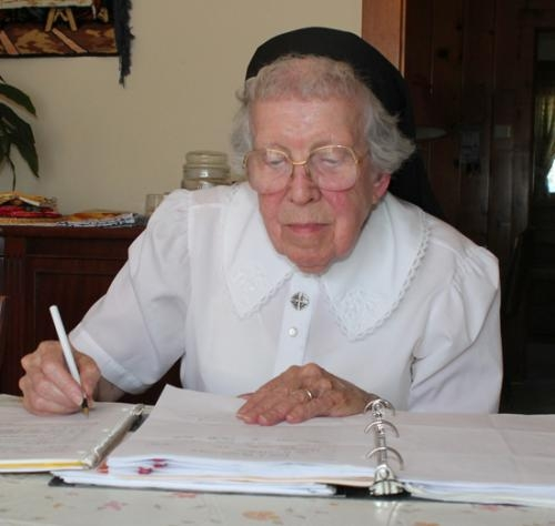 Sister Miriam Gill, the director of religious education at SS. Peter and Paul Catholic Church, updates student records at her Huntington home.