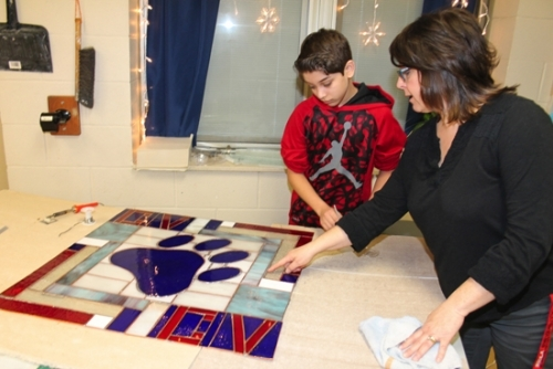 Crestview Middle School student Abimael Dominguez (left) receives instruction from art teacher Liesl Haupert on the next step in constructing a stained glass panel during class on Wednesday, Feb. 15. The panel is one of three that will be displayed in the foyer and office area of the school.