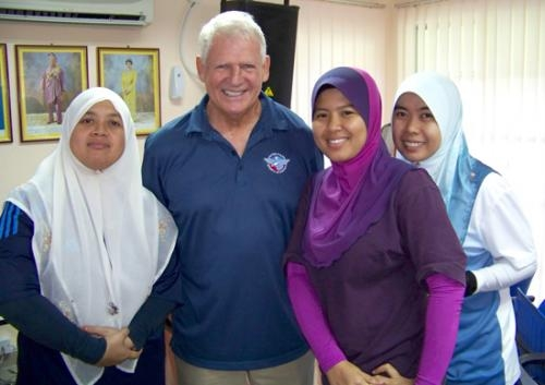 Huntington resident Stan Bippus spent 10 days in Malaysia as an instructor in physical education in a United States Sports Academy pilot program. Here, Bippus is pictured with three of his students.
