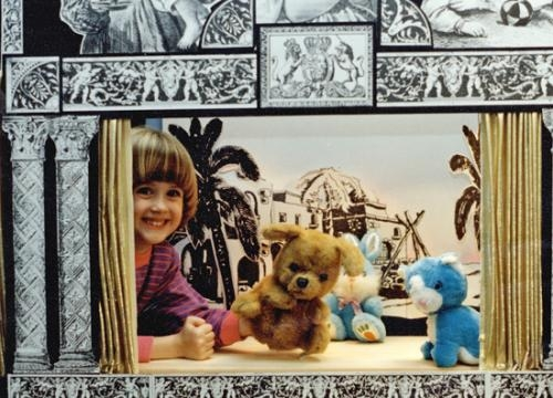 A young Joanna Stebing poses with puppets on the stage that her father, Thomas Stebing, built in the basement of their Fort Wayne home during her childhood.