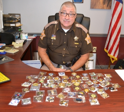 Huntington County Sheriff Terry Stoffel shows off some of his collection of challenge coins, medallions he's collected from other law enforcement agencies — as well as non-police groups — from across the country.