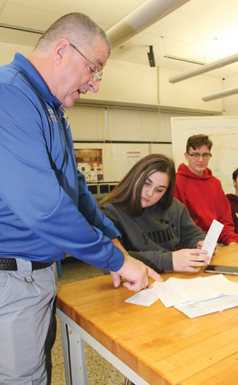 Huntington North High School Criminal Justice class teacher Terry Stoffel (left) goes over a pile of donations with student Jozzy Helbert, as student Nick Johnson watches. The class has set a goal to raise $5,000 for the annual Shop with a Cop program.