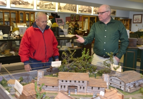 Huntington County Historical Museum Director Mark Stouder (right) and museum volunteer Jim Dinius look over a model of Huntington as it appeared around 1835. Stouder joined the museum as director late last year.