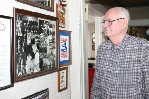 Bob Straight, of Huntington, the longtime coach of the Huntington High School boys' varsity basketball team, gazes at a picture in his house of the 1963-64 team that played for the state title.