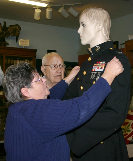 Linda Wilson, left, adjusts a jacket on a mannequin at the Huntington County Historical Museum recently as Richard Newell looks on. The two volunteers were preparing the Veteran's Day exhibit at the museum.