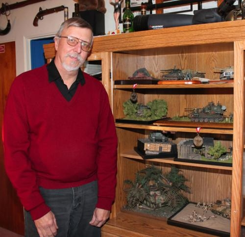 Dan Drake, of Roanoke, stands beside a cabinet at his home where his model tank dioramas are on display. Drake made models in his youth and decided to pick it back up as a serious hobby a few years ago.