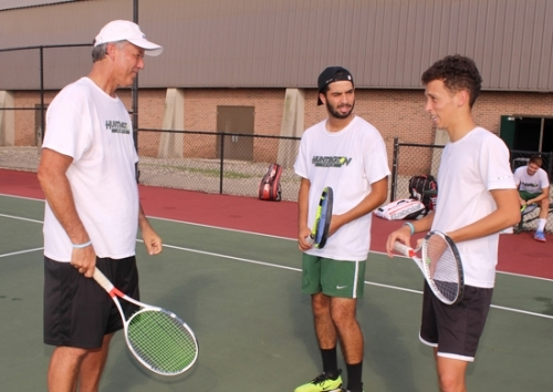 Kreg Eckert (left), head coach of the Huntington University men's tennis team, listens to a question from one of his players, Ignacio Poncio (right), while one of his other players, Giovanni Martinez, looks on. Poncio and Martinez hail from Argentina and Mexico, respectively, and represent two of many players from around the world who discovered Huntington through tennis.