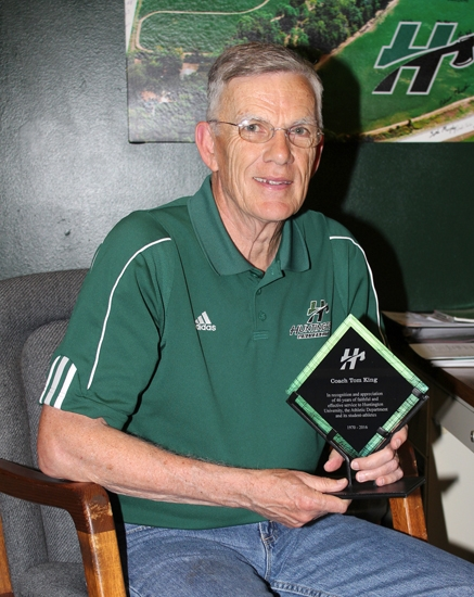 Tom King, the longtime head coach of Huntington University's track and cross country teams, sits in his office with an award recently given to him by the school thanking him for his 46 years of service. In March, King announced his retirement, which becomes effective at the end of May.