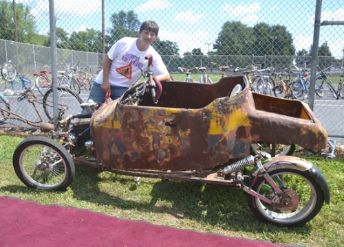 Tommy Johnson poses next to the pedal-powered car he cobbled together using the body of an old Idle Hour roadster, seven bicycles and other bits and pieces.
