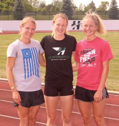 Lauren Johnson (left), Hannah Stoffel (middle) and Addy Wiley stand together on the King Stadium track at Huntington University. All three are successful distance runners at different points in their careers. Johnson and Stoffel are Huntington North High School graduates while Wiley is currently a student at the school.