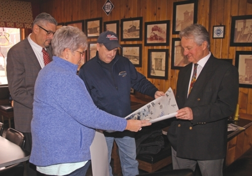 Ray Shearer (third from left), the chairman of the USS Indiana and USS Indianapolis commissioning committees, presents a picture of the latter vessel that was signed by the crew to Jean Anne Bailey (second from left), the owner of Nick's Kitchen, during a visit to the Huntington diner on Monday, Feb. 17. Shearer thanked Bailey for sending tenderloins to the crews of both vessels. The idea to do so was hatched by the Huntington County Commissioners. Also pictured are Commissioner Tom Wall (first from left) and Commissioner Rob Miller.