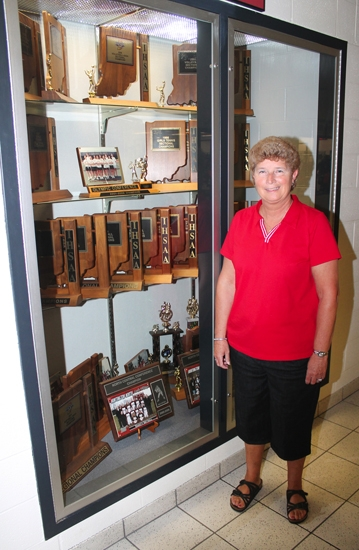 Phyllis Vance, a retiring Huntington North High School teacher and former coach, stands by a display case of trophies won by the softball team, which she started in 1985.