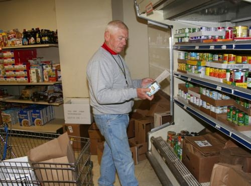 Love In the Name of Christ volunteer Ed Beckner, of Huntington, checks to make sure he's filling the correct order for a food pantry client on Friday, Dec. 27.