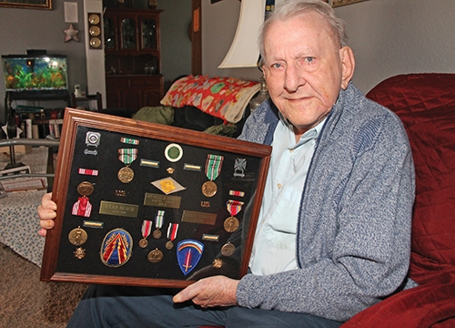 Paul Strevy, of Huntington, holds a framed collection of the medals he received as a result of his service in the United States Army during World War II. He was stationed in Great Britain, France, Belgium and Germany.