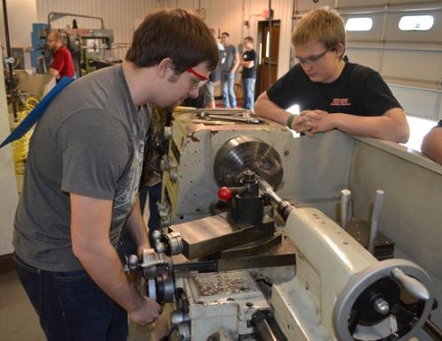 Huntington North High School's Tyler Spoonamore (right) looks on as John Milledge operates a lathe.