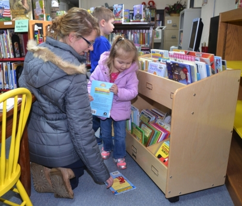 Angela LaMar (left) helps daughter Penelope LaMar select books from the new display bins at the Warren Public Library on Monday, Jan. 9, as Penelope's brother, Spencer LaMar, browses books in the background.