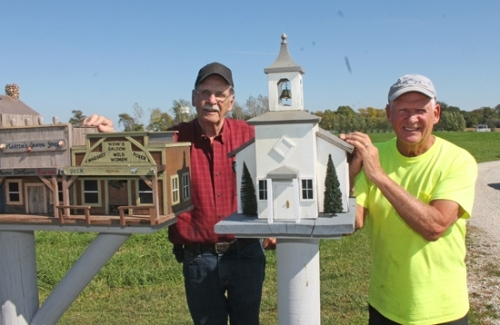 Jerry Martin (left) and Stan Bippus show off the miniature western town they and a few of their friends made, which is displayed along Bippus' property on CR 300W. The church is a replica of the Clear Creek Church, located at 750 N. Clear Creek Rd.