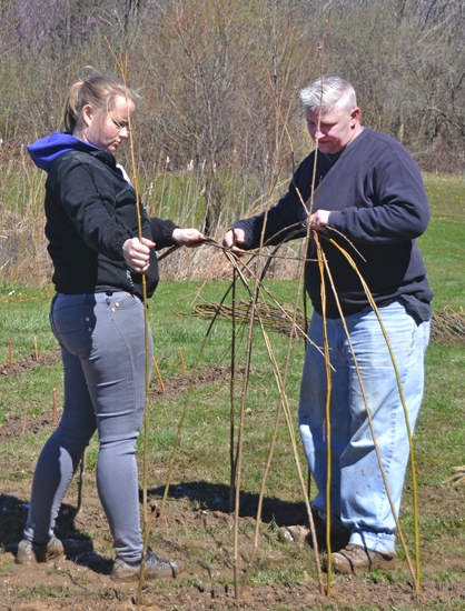 Sadie Misiuk (left) and Viki Graber plant willow branches on the banks of a pond at Salamonie Lake on Friday, April 7. The branches will eventually become a living tunnel, an installation put in place as part of the Indiana Arts Commission's Arts in the Parks program.
