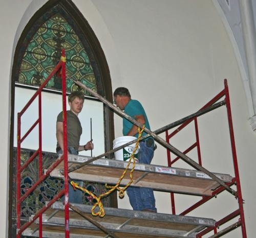 Peter Lupkin (left) and Larry Hormann, of William Lupkin Designs, reinstall the stained glass windows at SS. Peter and Paul Catholic Church on Friday, Sept. 7.
