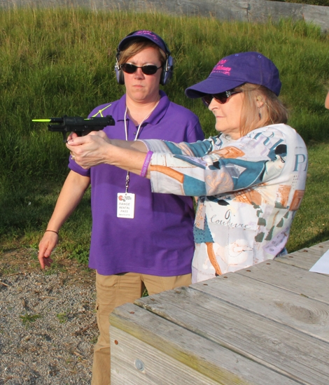 Under the watchful eye of The Well Armed Woman leader/instructor Alysha Wilson (left), Jo Ann Reed, of Andrews, practices taking aim at a target at the outdoor range at Hillside Shooting Sports, in Roanoke. The club had its first Roanoke chapter meeting on June 15.