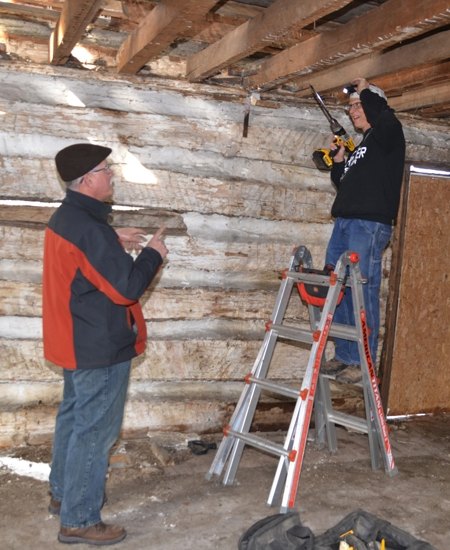 Markle resident Jeff Stockman (left) watches on Saturday, Jan. 21, as Darrin Rubino, a professor at Hanover College, extracts a sample of wood from a beam in a log home believed to be one of the earliest homes to be built in Markle.