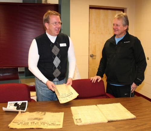Tim Allen (left), marketing director for the Parkview Huntington Family YMCA, takes a look at old newspapers with Youth Sports Coordinator Rob Miller that contain news about the 'Y,' shedding light on its history.