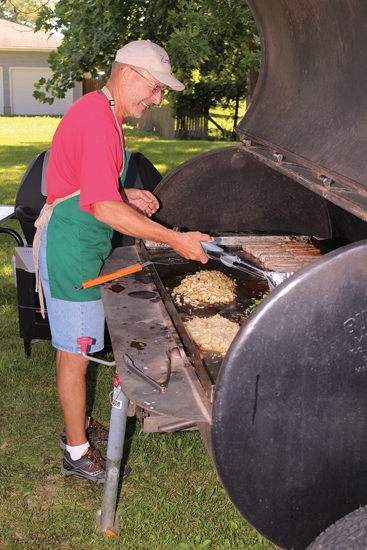 Steve Whetstone mans the grill, cooking up bratwurst and toppings at the Zanesville Ballpark during the Zanesville Lions Club Summer Festival last year. Food and other treats will again be offered at this year's festival, set for Saturday, July 28.