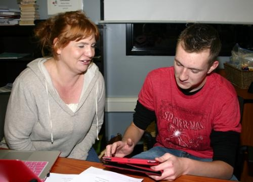 Lynn Brown (left), social studies teacher at Huntington North High School, helps senior Tyler Korthal (left) publish a journal entry online using his iPad.