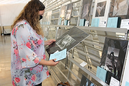 Judge Elysia Rodgers, of Fremont, peruses a photo entered in the black and white salon class of the photography project division on Thursday, July 23, at the Huntington County 4-H Fair.