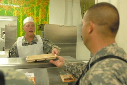 First Sgt. Charles Applegate, of Huntington, accepts a meal order from Spc. Stephen Hill on Thanksgiving Day at Bagram Air Field in Afghanistan.