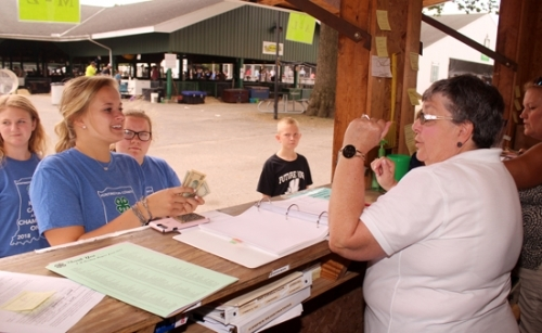 4-H'er Kalee Platt (left) picks up her premium money from the Huntington County 4-H Fair Auction from Carol Holmes (right), a volunteer with Purdue Extension Huntington County, on Thursday, July 26, at the Huntington County Fairgrounds office.