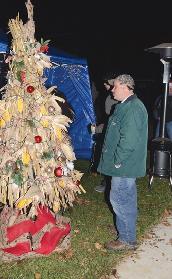 Jarrod Hahn, of Keystone, checks over the cornstalk Christmas Tree made by employees of Nutrien Ag Solutions of Warren at the Holiday Walk & Festival of Trees in downtown Warren last year. A record 41 trees will be on display at this year's event on Friday night, Nov. 22, from 5 p.m. to 8 p.m.