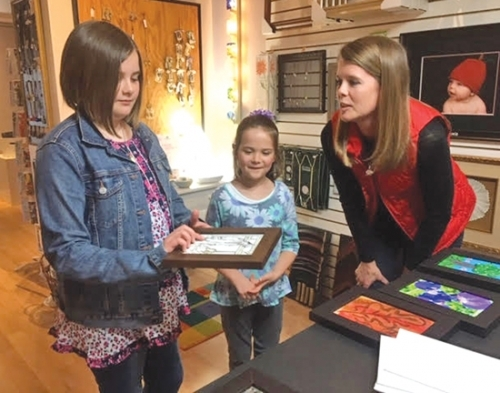 Sophia (left) and Olivia Kemp (center) check out some previous JeFFFest artwork with their mom Sarah Kemp prior to purchasing their canvases for this year's event. The official JeFFFest canvases are now available at Four Corners Custom Framing.