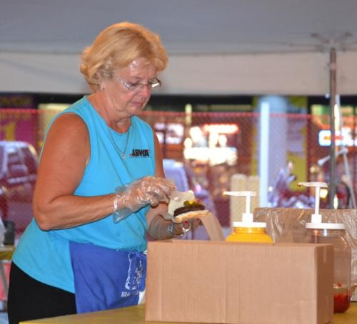 Marj Hiner garnishes a hamburger in the American Business Women's Association (ABWA) Brat Tent during the 2011 Heritage Days Festival. Hiner is the architect of the event, which has been running for 29 years.