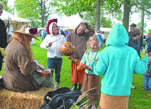 Stephanie Shultz (left) plays the dulcimer during last year's Forks of the Wabash Pioneer Festival as (from left) Eva Thomson, Hannah Thomson, Elizabeth Thomson and Shelby Cook (back to camera) play along by rattling dried gourds.