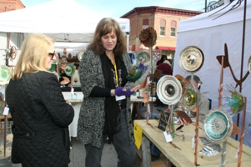 Artist Jeanne Carroll (right) shows a piece of her garden art to Sandy McGill, of Roanoke, during A Renaissance in Roanoke in 2014. This year's arts festival will be held in downtown Roanoke on Saturday, Oct. 20, from 10 a.m. to 5 p.m.