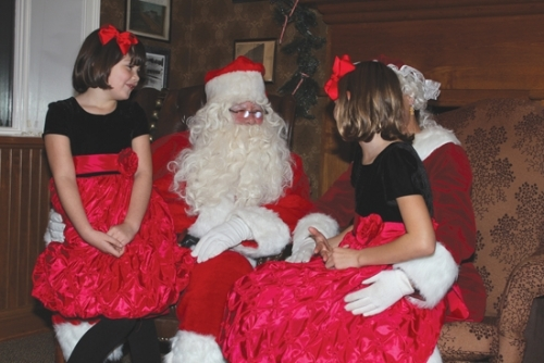 Santa Claus and Mrs. Claus listen to the Christmas wishes of Anna Screeton (left) and sister Zoe during Christmas in the Village in the Roanoke Public Library last year. Christmas in the Village will take place this year Friday and Saturday, Dec. 1 and 2.