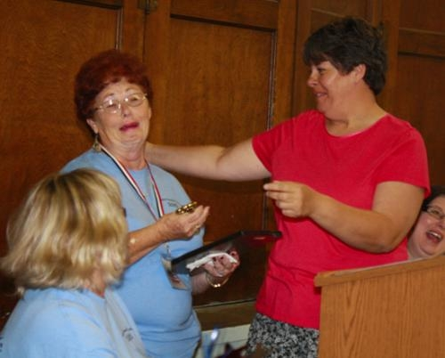 "Bonnie Boxell (left) tearfully receives a hug and the key to the town of Warren from Warren Town Council President Julia Glessner after she and her late husband, ""Big Ron"" Boxell, were named winners of the Samuel Jones Pioneer Award on Friday, June 29."
