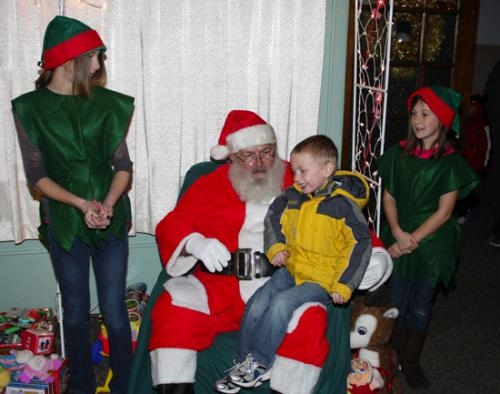 Santa Claus, flanked by helpers Grace Asher (left) and Alivia Harmon, listens to Ceaten Brubaker detail his wish list during as appearance at the Knight-Bergman Center during the 2012 Winter Warrenland celebration.