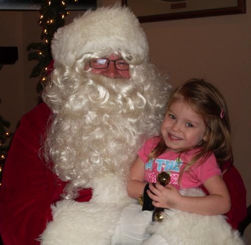 Melissa Caley sits on Santa Claus' lap during one of his visits to Pathfinder Kids Kampus, in Huntington, last week. He was on hand to hear Christmas wishes and take pictures with the children.