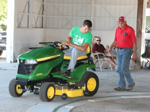 Tyler Stephan competes in the senior lawn and garden class of the 4-H Tractor Operators' Contest held Sunday, July 8, at the Parkview Huntington Hospital Show Arena. He is followed by judge Marc Dennis, of Huntington. Stephan took first place in his class.