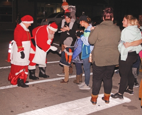 Santa Claus and Mrs. Claus are greeted by children and their adults upon arriving in Warren on one of the town's fire trucks last Christmas. The Clauses will make their annual pre-holiday trip to Warren this Friday night, Nov. 29.