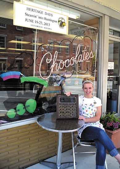 Abby Hoffman, an employee of The Party Shop in downtown Huntington, holds the plaque the shop received after winning its category in the Heritage Days Window Display contest. Hoffman designed the train display inside the window and painted the window.