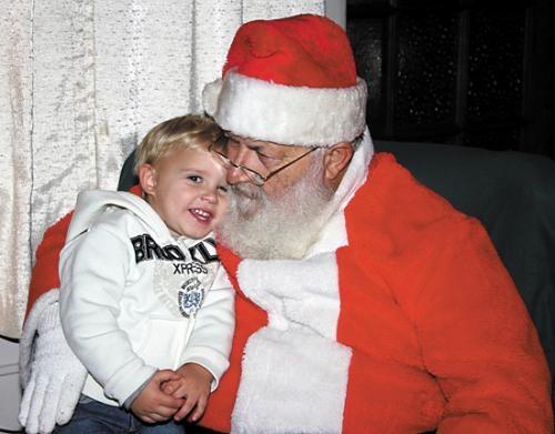 Elijah Flippen shares a hug with Santa Claus during last year's Winter Warrenland celebration. Santa will return to Warren on Friday, Nov. 23.