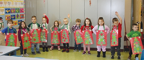 """Parkview Huntington Family YMCA Pre-K students (from left) Jonah Jeffers, Veda Brown, Caleb Cureton, Lyriel Plasterer, Jozie Medina, Jackson Cutshall, Brantley Myers, Violet Lederle, Adali Wisialowski, DJ Patterson and Konner Covey practice a performance of """"Rockin' Around the Christmas Tree"""" on Thursday, Dec. 17. The students later performed the song as it was recorded and uploaded to the YMCA's YouTube page. In light of the COVID-19 pandemic, educators made the decision to air the students' program virtually, rather than inviting an in-person audience. The program was part of the students' celebration during the last day of class before the holiday break."""
