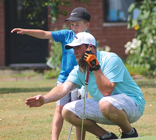Father and son team, Nolan and Daniel Chenoweth, of Van Buren, discuss their course of action for putting the ball into hole two during the Junior/Senior golf tournament at Etna Acres on Saturday, July 11.