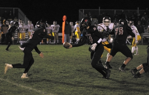 Huntington North quarterback Brett Kaylor (middle) hands the ball off to running back Logan Hippensteel during a sectional game against visiting McCutcheon on Friday, Oct. 27. The Vikings lost 42-7, bringing their season to an end.
