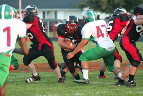 Austin Rosen (middle), a fullback for the Huntington North varsity football team, braces for impact as he rushes the ball in a game against visiting Anderson on Friday, Sept. 14. The Vikings won 62-49.