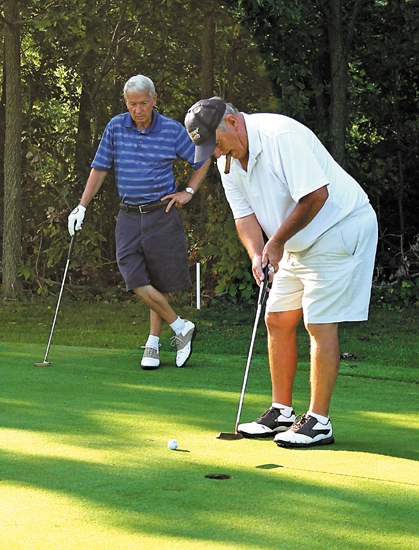 Al Shockley (right) tries to sink his putt on the fourth hole of Etna Acres Golf Club while Dan Bickel looks on during play in the super senior division of the Huntington County Amateur Golf Tournament on Sunday, Aug. 25. Bickel won the division.